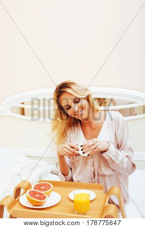young beauty blond woman having breakfast in bed early sunny morning, princess house interior room, healthy lifestyle concept