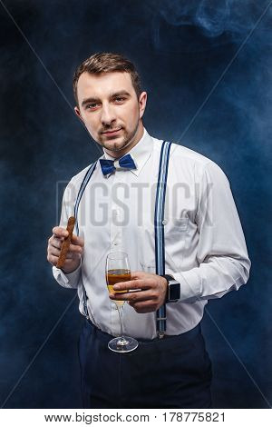 Portrait of a handsome man in bow-tie and suspenders holding glass of beverage and cigar while looking at camera. Smoke on background. Studio shot
