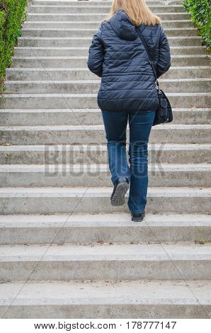 Woman Going Upstairs In An European City