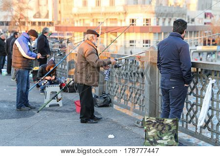 ISTANBUL TURKEY - MARCH 01 2017: Fishers fishing on Galata Bridge. Galata Bridge is the most popular destinations for entertainment and travel of Istanbul.