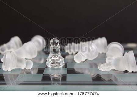 Chess of glass on a black background. Pawn surrounded by the defeated opponent. Business concept wins.