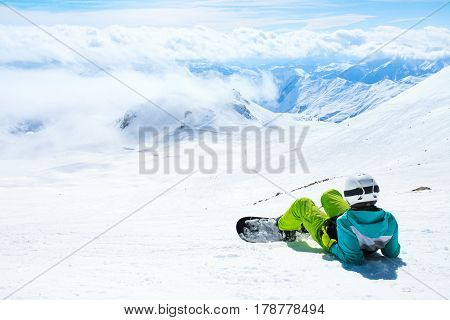 Rear view of famale lying on snow and looking forward on mountains