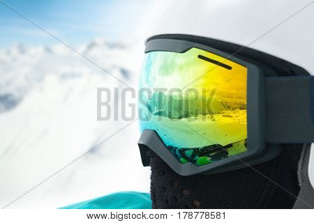 A mountains reflected in the ski mask. Portrait of snowboarder at the ski resort
