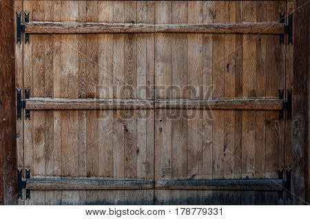 Closed weather worn dilapidated wooden doors entrance in wood paneled building
