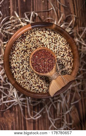 Mixed and red raw quinoa seeds in wooden bowl on a brown background. Rustic style, top view