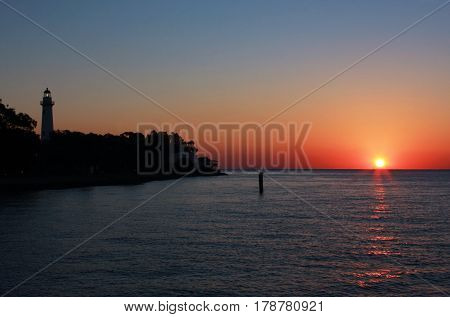Sun rises over the Atlantic Ocean and the lighthouse on St. Simon's Island, Georgia in springtime