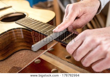 Close up of the hands of an instrument maker, filing the frets of an acoustic guitar