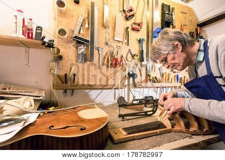Luthier concentrating on carving a lute, in a cluttered workshop, surrounded by tools and semi finished instruments.