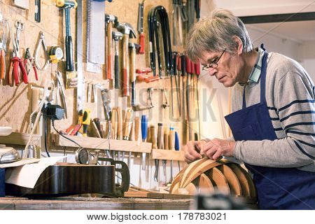 An authentic, instrument maker, presicely carving the body of a halfway finished lute on his workbench, surrounded by the tools of the trade of a passionate craftsman. poster