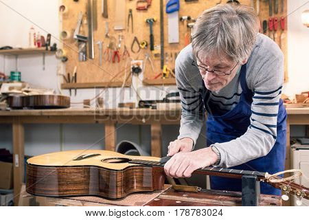 Luthier filing the frets of an acoustic guitar on the workbench