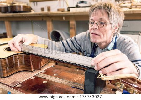 Man presicely measuring the distances between frets on the neck of a guitar