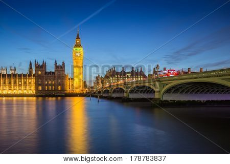 London England - The Big Ben Clock Tower and Houses of Parliament with iconic red double-decker buses at city of westminster by night