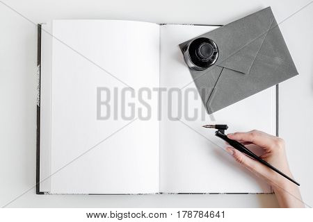 Writer workplace with tools, hand and envelope on white table background top view mock up