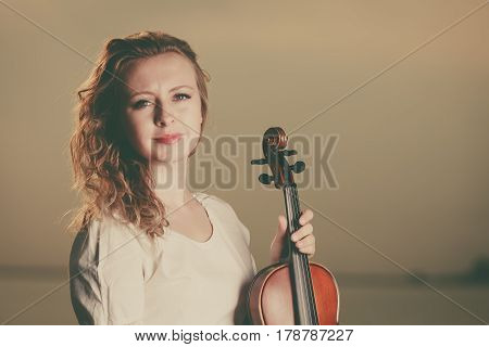 Music love hobby and everyday passion concept. Woman on beach near sea holding violin during sunset