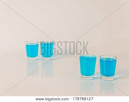 Four Glasses Of Blue Kamikaze, Glamorous Drink, Mixed Drink Poured Into Shot Glasses