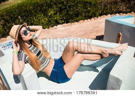 Relaxed Beauty Woman Lyeing On Garden Couch In Hotel Park. Summer Vocation.
