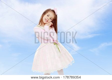 Dressy little girl long blonde hair, beautiful pink dress and a rose in her hair.She holds his palm near his face.On the background of summer blue sky and fluffy clouds.