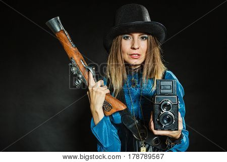 Photography and retro style. Young vintage attractive girl holds old aged camera. Steampunk photographer with gun pistol.