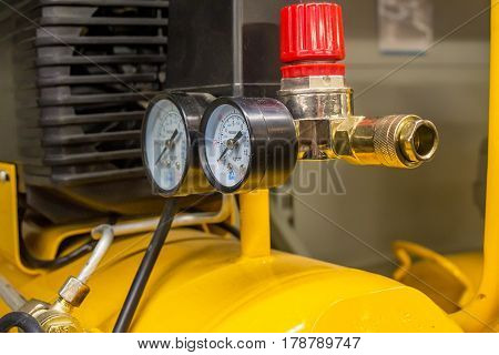 Closeup of colorful manometers on yellow compressor