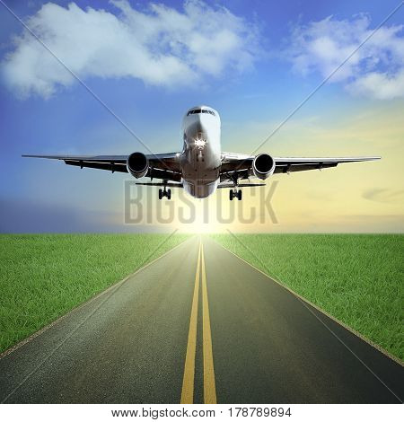 One passenger airplane takes off from a runway. Beautiful blue cloudy sky and sunset background. Grass field around. Travel concept