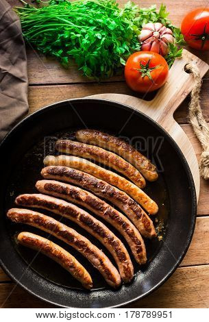 Delicious fried sausages with golden crust in iron cast pan fresh parsley tomatoes on wood table top view