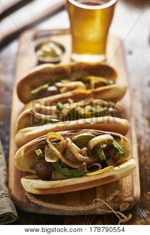 three bratwurst sausages with grilled onions and bell peppers