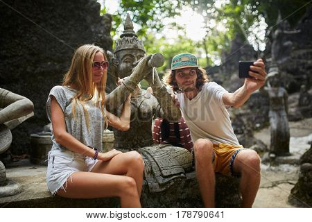 tourist couple taking selfie with ancient buddhist statue in thailand