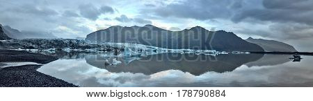 Glacial lagoon in Iceland in the fall. Cloudy foggy weather, mountains on the horizon. The glacial lake reflects the sky, glacier and mountains. Panoramic shot