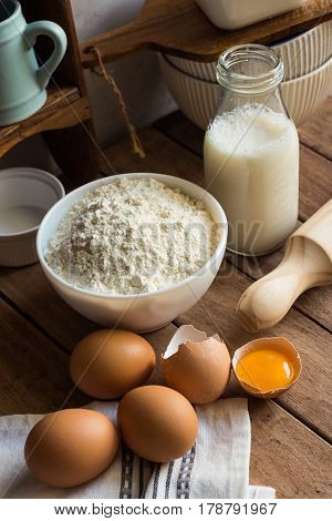 Baking ingredients flour eggs open yolk milk rolling pin cupboard rustic kitchen interior utensils