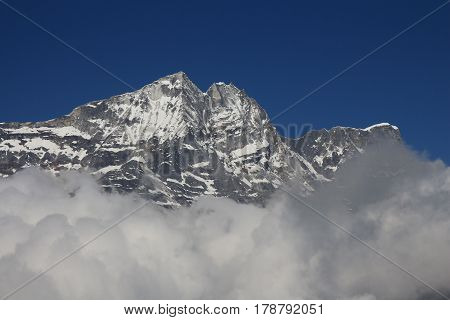 High mountain in the Everest National Park reaching out of clouds.