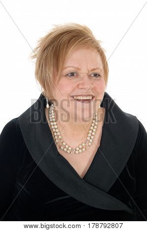 A smiling senior woman in a black dress smiling in a portrait image wearing a peal necklace isolated for white background.