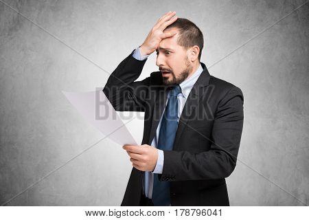 Desperate businessman reading a document