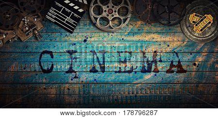 Cinema concept of vintage film reels, clapperboard and projector on old wooden background.