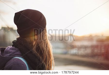 Hipster girl walking on the city street at sunset