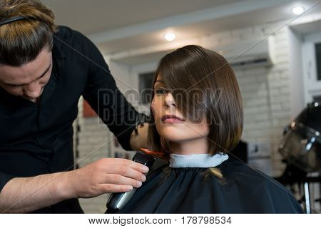 Male hairdresser does a haircut to pretty woman in the beauty salon.