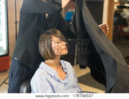 Male hairdresser is preparing Apron for pretty woman in the beauty salon.