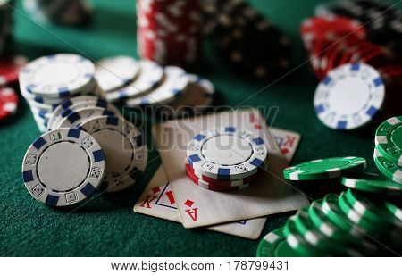 set of gambling chips and cards on green baize gambling casino