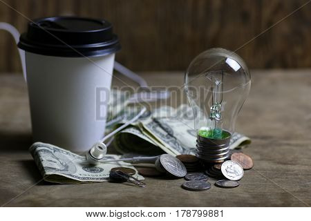 coins and crumpled money with tungsten lamp filament
