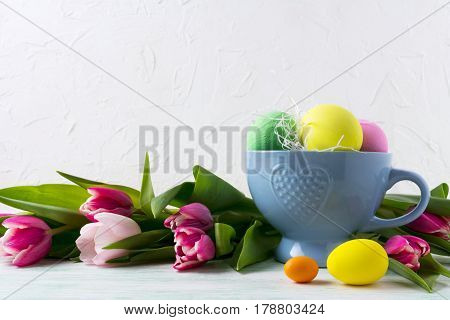 Easter Hand Painted Eggs In Blue Cup And Pink Tulips Background