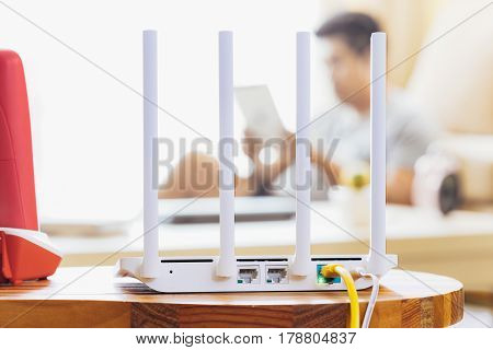 closeup of a wireless router and a man using Tablet on living room at home ofiice