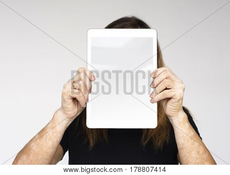 Woman is holding a digital device on her face