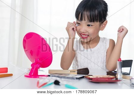 Asian Chinese Little Girl Applying Makeup With Cosmetics