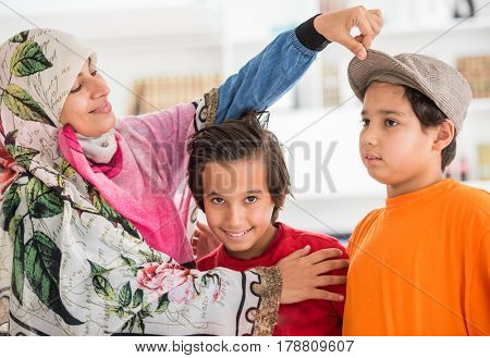 Arabic Muslim mother with sons at modern home