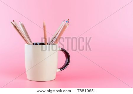 Color Pencil in coffee mug on pink background with copy space