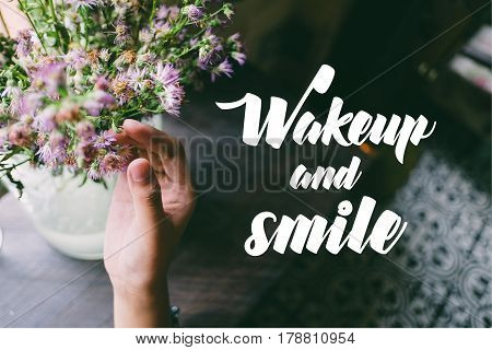Life quote. Motivation quote on soft background. The hand touching purple flowers. Wakeup and smile.