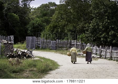 Plimoth Plantation, Plymouth, Massachusetts - September 10, 2014 - Wide view from the back of two pilgrim women walking up a path woven baskets in hand at Plimoth Plantation with a fence trees and foliage on a bright sunny day in September.