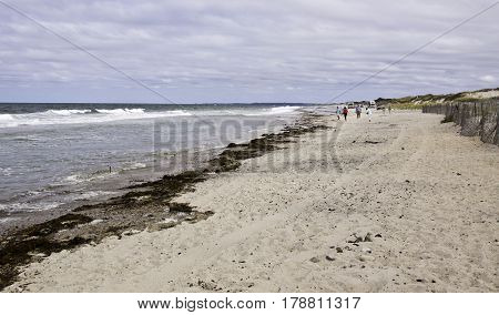 Barnstable, Massachusetts - September 12, 2014 -- Wide view of the shore at Sandy Neck Beach, Barnstable off Cape Cod Bay, Massachusetts with small waves rolling into the shore and people walking on the beach in the distance on a bright sunny day