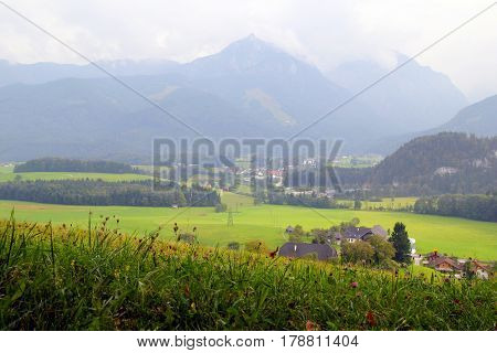 Travel To Sankt-wolfgang, Austria. The View On The Green Meadow With The Mountains On The Background