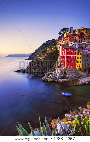 Riomaggiore village on cliff rocks and sea at sunset. Seascape in Five lands Cinque Terre National Park Liguria Italy Europe. Long Exposure