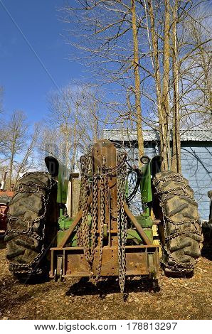 Chains for greater traction in mud, ice, and snow have been placed on the rear tire of a tractor